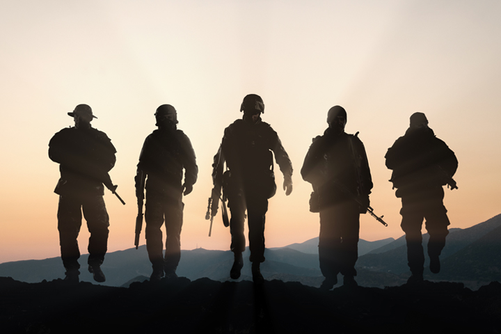 Five military members at sunset
